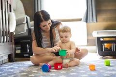 Kinderkleinkind, das zu Hause Spielwaren oder Kindergarten mit Mutter spielt stockfoto