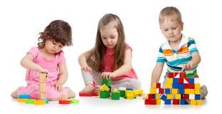 Kinderkleinkinder, die das Holzklotzspielzeug lokalisiert auf Wei? spielen stockbild
