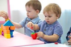 Kinderkleinkinder spielen buntes Lehmspielzeug im Kindergarten lizenzfreie stockfotos