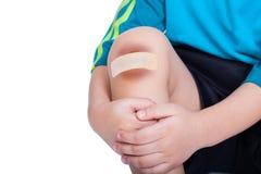 Kinderknie mit einem Gips (für Wunden) und Quetschung Stockbilder