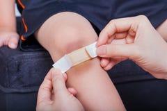 Kinderknie mit einem Gips (für Wunden) und Quetschung Lizenzfreie Stockfotos