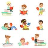 Kinderlesebücher und Genießen der Literatur-Sammlung netter Jungen und Mädchen, die lieben, das Sitzen und das Legen zu lesen Lizenzfreie Stockfotos