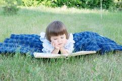 Kinderlesebuch, das auf, lächelndem nettem kleinem Mädchen des Magens, den Kindern Bildung und Entwicklung im Freien liegt lizenzfreie stockfotografie