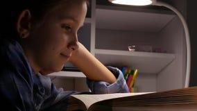 Kinderlesung in der Nacht, Schulmädchen, das in der Dunkelheit, lernendes Kind, Hausarbeit studiert stock footage
