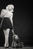 Kinderlijke vrouw met hondstuk speelgoed op zwarte royalty-vrije stock foto's