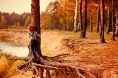 Kindermädchen, das alte Kiefer auf dem Weg auf Herbstflussseite klettert Stockfoto