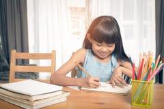 Kindermädchen, das auf dem Tisch zeichnet stockbild
