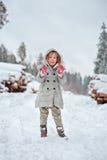 Kindermädchen, das auf dem Weg im schneebedeckten Wald des Winters spielt Stockbilder