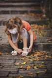 Kindermädchen, das auf Steinstraße mit Schritten am warmen Herbsttag sitzt Stockfotos