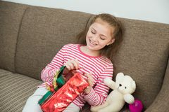 Kindermädchen, das in der Hand ein Geschenk hält und rote Geschenkbox öffnet lizenzfreie stockbilder
