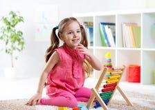 Kindermädchen, das mit Abakus spielt Stockbild