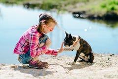 Kindermädchen, das mit Boston-Terrierhund auf dem sandigen Flussba spielt Lizenzfreie Stockfotografie