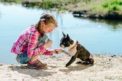 Kindermädchen, das mit Boston-Terrierhund auf dem sandigen Flussba spielt Lizenzfreies Stockfoto