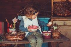 Kindermädchen, das mit Ostereiern und handgemachten Dekorationen im gemütlichen Landhaus spielt Stockbilder