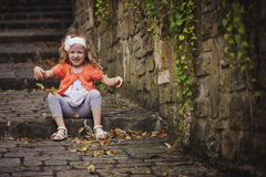 Kindermädchen, das Spaß hat und Blätter beim Sitzen auf alter Steintreppe wirft Lizenzfreies Stockbild