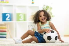 Kindermädchen, das Spielwaren am Kindergartenraum spielt Lizenzfreie Stockbilder