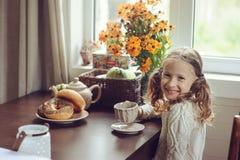 Kindermädchen, das zu Hause im Herbstmorgen frühstückt Aus dem wirklichem Leben gemütlicher moderner Innenraum im Landhaus Lizenzfreies Stockbild