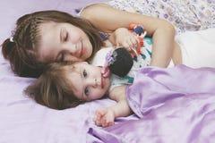 Kindermädchen, die im Bett liegen Lizenzfreie Stockfotografie
