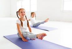 Kindermädchen, die Yoga und Gymnastik in der Turnhalle tun stockfoto