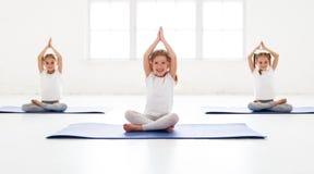 Kindermädchen, die Yoga und Gymnastik in der Turnhalle tun stockbilder