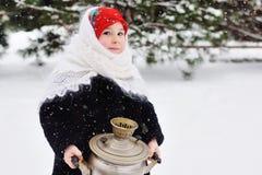 Kindermädchen in einem Pelzmantel und Kopftuch in der russischen Art, die einen großen Samowar auf dem Hintergrund des Schnees un stockfotografie