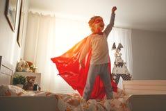 Kindermädchen in einem Superheldkostüm mit Maske und rotem Mantel lizenzfreies stockbild