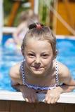 Kindermädchen im blauen Bikini nahe Swimmingpool Heißer Sommer Stockbilder