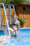 Kindermädchen im blauen Bikini nahe Swimmingpool Heißer Sommer Lizenzfreies Stockbild
