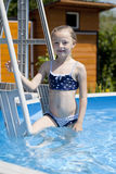 Kindermädchen im blauen Bikini nahe Swimmingpool Heißer Sommer Stockfotografie