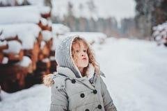 Kindermädchen im grauen Mantel auf dem Weg im schneebedeckten Wald mit Baumholzschlag Lizenzfreies Stockbild