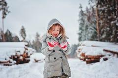 Kindermädchen im grauen Mantel auf dem Weg im schneebedeckten Wald mit Baumholzschlag Stockfoto