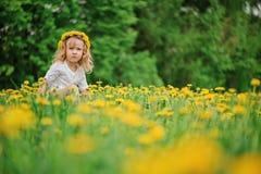 Kindermädchen im Löwenzahnkranz auf Frühlingsblumenfeld Lizenzfreie Stockfotos