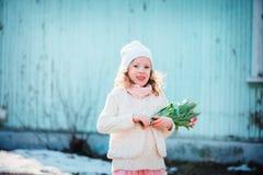 Kindermädchen mit Blumenstrauß von den Tulpen, die Spaß auf dem Weg im Vorfrühling haben Lizenzfreie Stockfotografie