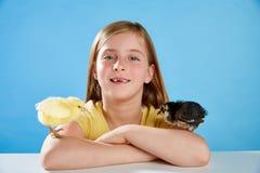 Kindermädchen mit den Küken, die auf Blau spielen Stockfotografie