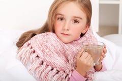 Kindermädchen mit einer Schale heißem Tee im Bett Lizenzfreie Stockfotografie