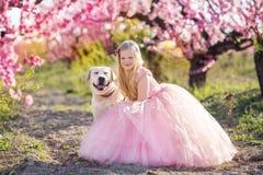Kindermädchen mit Labrador-Hund in blühendem Garten Lizenzfreie Stockfotografie