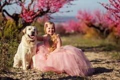Kindermädchen mit Labrador-Hund in blühendem Garten Stockfotografie