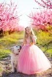 Kindermädchen mit Labrador-Hund in blühendem Garten Stockfotos