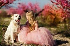 Kindermädchen mit Labrador-Hund in blühendem Garten Lizenzfreie Stockbilder