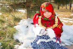 Kindermädchen in russisches pavloposadskie Volksschal auf Kopf mit Blumendruck und mit Bündel Bageln auf Hintergrund des Schnees stockbilder