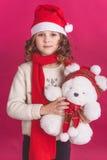 Kindermädchen in Sankt-Hut auf rotem Hintergrund lizenzfreie stockfotografie