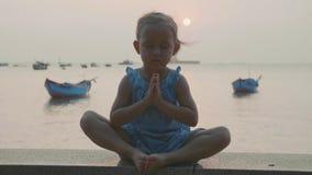 Kindermädchen sitzt auf dem hölzernen Pier in der Lotoshaltung und meditiert in der Zeitlupe stock video