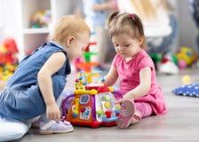 Kindermädchen spielen zusammen pädagogische Spielwaren im Spielzimmer lizenzfreie stockfotos
