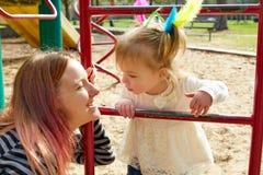 Kindermädchen und -mutter, die Spielplatzleiter spielen Lizenzfreie Stockbilder
