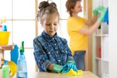 Kindermädchen und -mutter machen Reinigung im Raum zu Hause stockfoto
