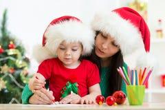 Kindermädchen- und -mutterschreibensweihnachtsbuchstabe zu Stockfoto