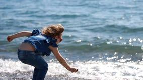 Kindermädchen wirft Steine von der Küste in das Meerwasser stock footage