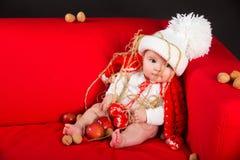 Kindermädchenbaby mit Weihnachtsdekoration Stockbilder