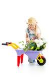 Kindermädchengärtner, der an eingemachten Blumen sich interessiert Stockfoto