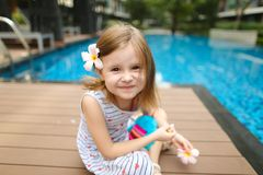 Kindermädchenlächeln an der Kamera, die nah an dem Swimmingpooltragen sitzt lizenzfreies stockfoto